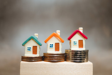 Miniature colorful house on stack coins using as property and business concept