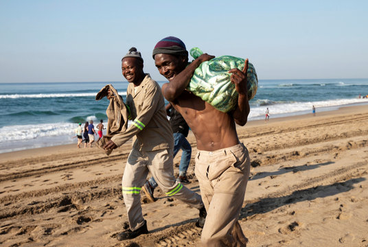 A man leaves the beach with a bag full of sardines during the sardine run in Umgababa