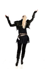 full length portrait of blonde girl wearing lack fantasy warrior outfit. standing pose wit bak to the camera. isolated on white studio background.