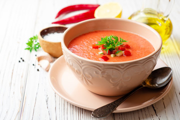 Gazpacho soup in bowl on white wooden background. Traditional spanish dish.