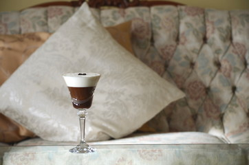 Espresso Martini cocktail, specialty alcoholic coffee drink in a crystal stem glass on a table by the couch. Relaxation at home.