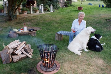 Young blond woman sits with her Golden Retriever and border collie by the campfire - young woman enjoys the warm summer evening at the campfire with her dogs and a glass of wine