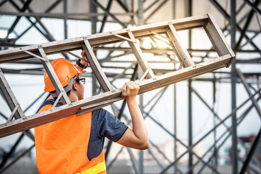 Young Asian maintenance worker with orange safety helmet and vest carrying aluminium step ladder at construction site. Civil engineering, Architecture builder and building service concepts