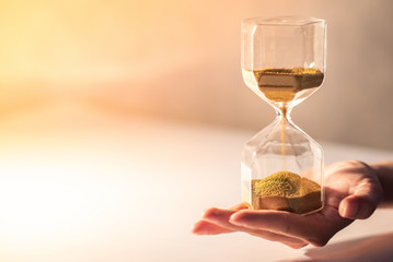 Close up of brown sand running through the shape of modern hourglass on male hand.Time passing and running out of time. Urgency countdown timer for business deadline concept with copy space