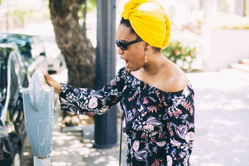 Young woman looking at parking meter
