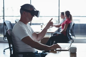 Businessman using virtual reality headset at desk
