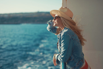 Blonde woman in hat on cruise ship looking away
