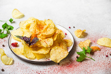 Dish with potato chips on a gray background