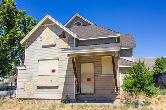 Abandoned Home With Boarded Up Windows & Doors