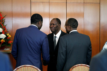 Ivory Coast President Alassane Ouattara shakes hands with the members of the new government during the first cabinet meeting at the presidential palace in Abidjan