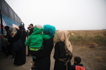 Syrians wait to board a bus just after they crossed the armistice line from Syria to the Israeli-occupied Golan Heights to get medical treatment in Israel