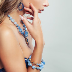 Female body with jewelry necklace, bracelet and earrings with blue gem