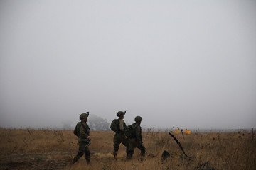Israeli soldiers patrol the area where Syrians cross the armistice line from Syria to the Israeli-occupied Golan Heights to get medical treatment in Israel