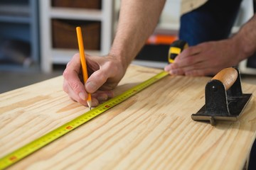 Male carpenter measuring and marking wood in workshop