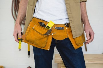 Male carpenter with tool belt in workshop