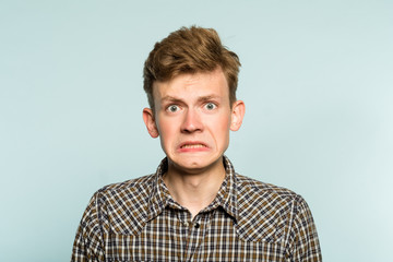 awkward gawky fumbling oafish dorky man facial expression. portrait of a young guy on light background. emotion facial expression. feelings and people reaction.