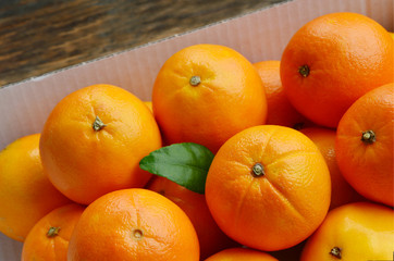 A lot of Sweet oranges in the paper box on wooden floor.  The fruit of the citrus.