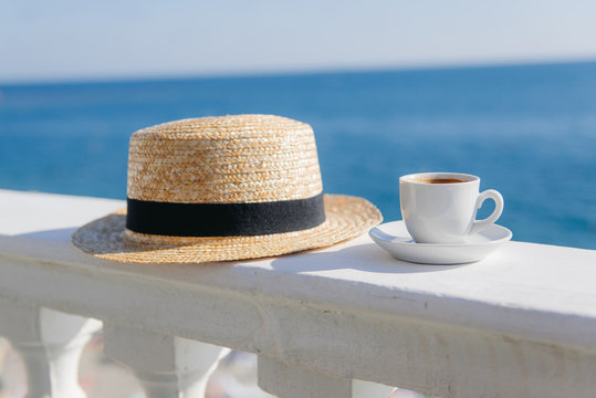 Cup of coffee next to a straw hat on a wall