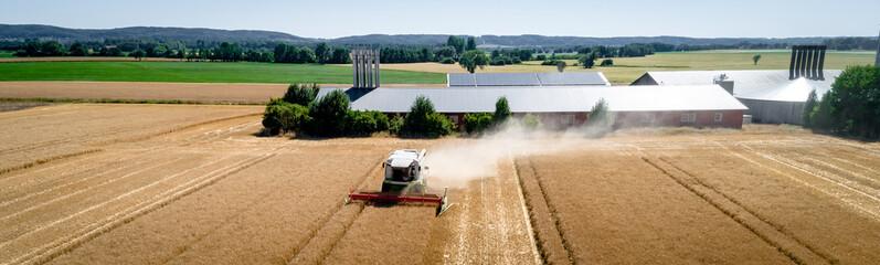 Getreideernte in Norddeutschland - Luftbild, Mähdrescher beim Dreschen vor einem Bauernhof