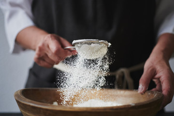 Slow motion shot of aged female hands sifting flour by sieve in wooden bowl.