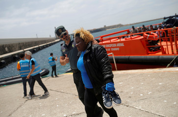 A migrant woman is helped by a Spanish civil guard after arriving on a rescue boat at the port of Tarifa