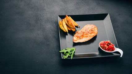 Baked chicken fillet with sesame seeds, potatoes and sauce. On a wooden background. Top view. Copy space.