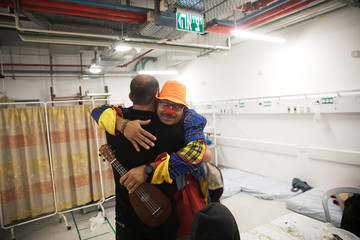 An Israeli medical clown hugs with a Syrian man who crossed the armistice line from Syria to the Israeli-occupied Golan Heights to help sick people get medical treatment in Israel