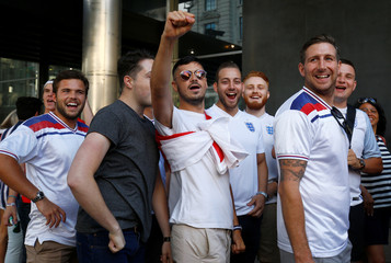England fans queue outside a sports bar, before the screening of the England v Croatia World Cup semi-final, in central London