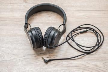 Black headphone put on wooden foor.
