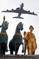 An AWACS aircraft flies over statues of the Arc de Triomphe du Carrousel during a rehearsal of the traditional Bastille Day military parade in Paris