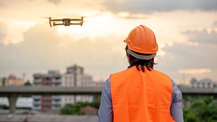 Young Asian engineer man flying drone over construction site during sunset. Using unmanned aerial vehicle (UAV) for land and building site survey in civil engineering project. Wall mural