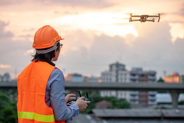 Young Asian engineer man flying drone over construction site during sunset. Using unmanned aerial vehicle (UAV) for land and building site survey in civil engineering project.