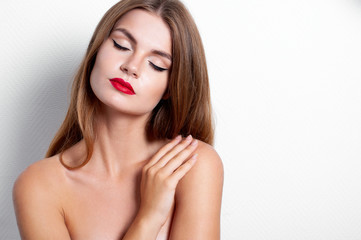 Close-up fashion portrait of young beautiful woman with Hollywood make up, red lips and fair hair in studio. Naked shoulders, right hand is on the left shoulder, closed eyes. Horizontal.
