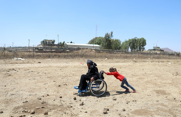 An Internally displaced girl pushes a woman on a wheelchair near the Israeli-occupied Golan Heights in Quneitra