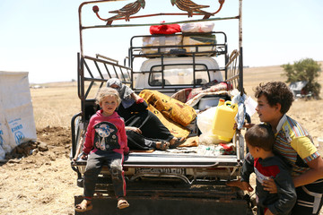 Internally displaced girl from Deraa province sits at a back of a truck near the Israeli-occupied Golan Heights in Quneitra