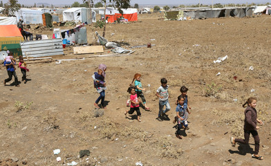 Internally displaced children from Deraa province run together near the Israeli-occupied Golan Heights in Quneitra