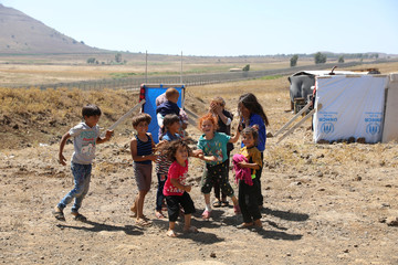 Internally displaced children from Deraa province play together near the Israeli-occupied Golan Heights in Quneitra