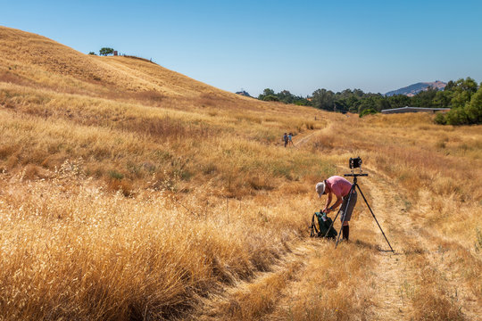 A man is setting up a large format camera on a path in California's golden grasses. Hills rise up behind him. He is wearing a red shirt. A blue sky is in the background.