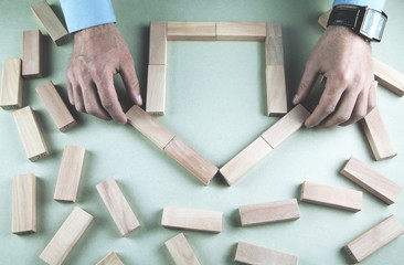 Businessman making model house with wooden blocks.
