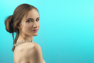 A beautiful girl with naked shoulders and nude makeup wearing a fashionable necklace with crystals. Isolated on blue. Copy space