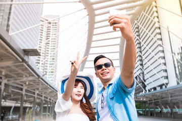 Funny young couple  takes selfie portrait on the landmark bridge at Bangkok, Thailand. Travel in asia concept