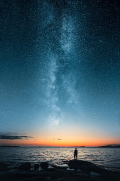 Silhouette of a man looking up on stars of the milky way with last light of sunset glows on the horizon