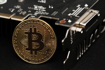 close up of golden bitcoin coin with graphic card isolated on black background