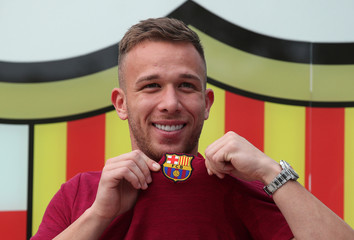 Brazilian soccer player Arthur Melo poses in front of a FC Barcelona logo at their offices next to Camp Nou stadium in Barcelona
