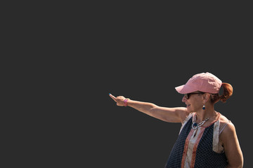 Isolated woman baby boomer dressed casually with pink hat on gray background pointing to empty copy space