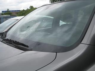broken car windshield, dent on glass, trowel on glass, replacement glass, exterior view