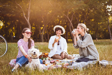 Beautiful girls taking photos on polaroid camera happily spending time on picnic with little dog in city park