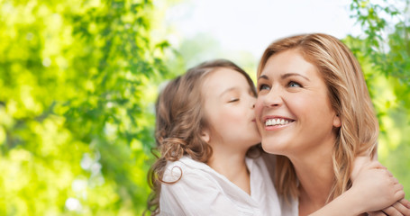 family, motherhood and people concept - happy daughter hugging and kissing her mother over green natural background