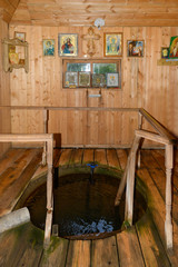 A hole with spring holy water in a small wooden chapel