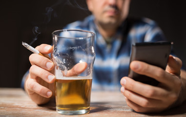 alcoholism, alcohol addiction and people concept - male alcoholic with smartphone drinking beer and smoking cigarette at night